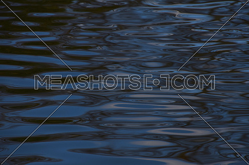 Colorful blue ripples and waves running on water surface texture background close up