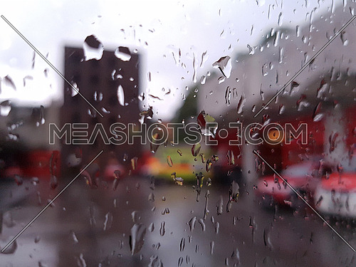 Firemen's tears concept: fire engines at a fire station in the rain from behind a glass covered in raindrops background