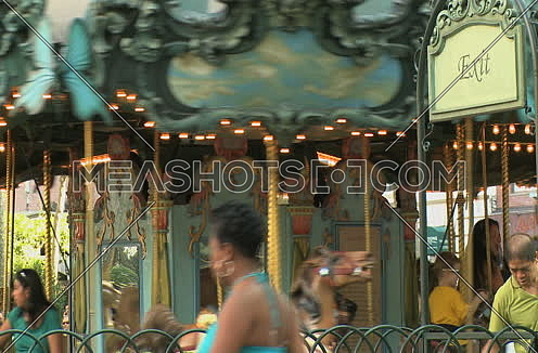 Medium shot for for Carousel spinning while adults and kids having fun in New York city at day.