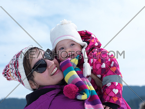 happy family on winter vacation, portrait of mom and cute little girl have fun and slide with fresh snow in background