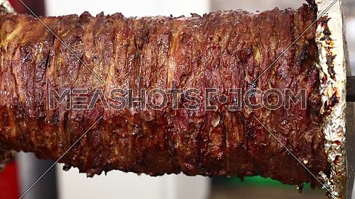 Close up beef meat Turkish doner kebab, Greek gyros or Arabian shawarma roasted and smoked in rotisserie over char grill, low angle side view