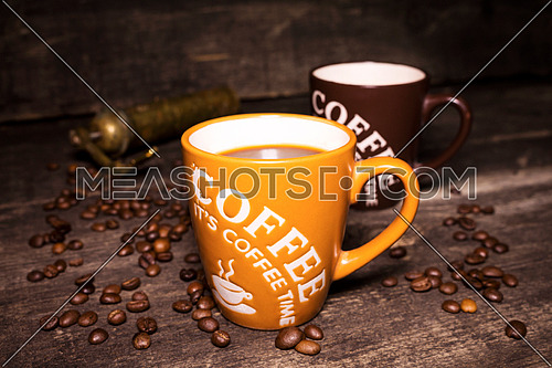 Coffee cup with coffee beans on wooden background