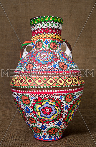 A colorful Egyptian handcrafted artistic ornate pottery jar on a sackcloth background. one of the art works of Ebtessam ElGohary, a contemporary Egyptian artist specialized in pottery painting art. Decorations are inspired by the Mandala style