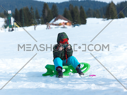 happy young boy have fun on winter vacatioin, sledding children on fresh snow at sunny day outdoor in nature playing games on mobile phone, addiction concept