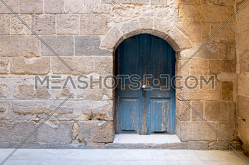 Blue wooden stained aged vaulted ornate door and stone wall, Medieval Cairo, Egypt