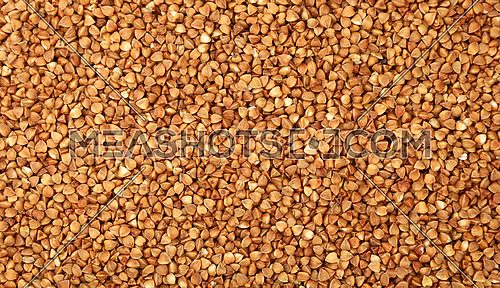 Dried brown buckwheat (Fagopyrum esculentum) groats close up pattern background, elevated top view