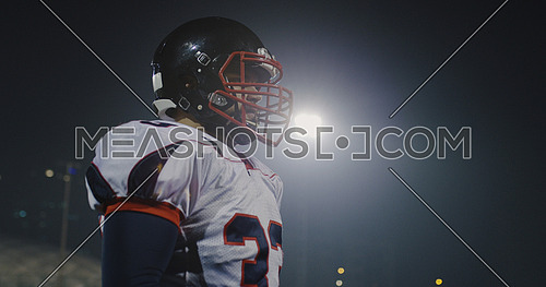 portrait of young confident American football player  standing on field at night
