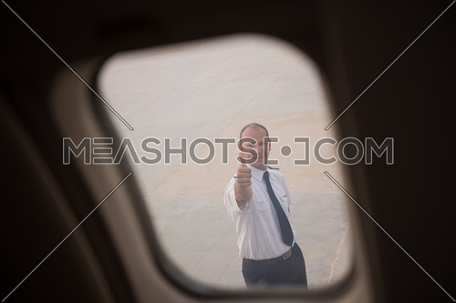 Young middle eastern successful pilot walking towards private jet giving thumbs up gesture