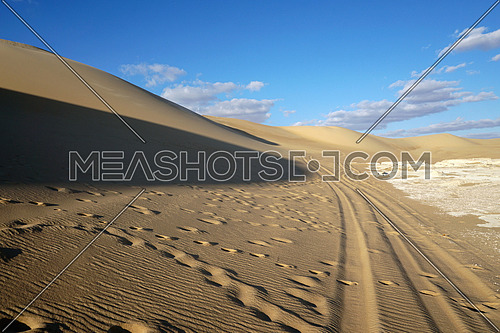 Landscape background of Safari cars track paths and foot steps on high curvy sand dunes in sunlight with cloudy blue sky in Siwa Oasis, Egypt Tourism