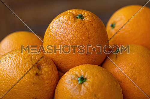 Lots of fresh oranges fruits plucked from branch of orange tree