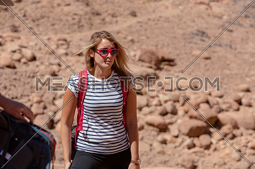 Long shot for a female tourist wearing a pink glasses and travel backpack taking exploring at Sinai Mountain for wadi Freij at day.