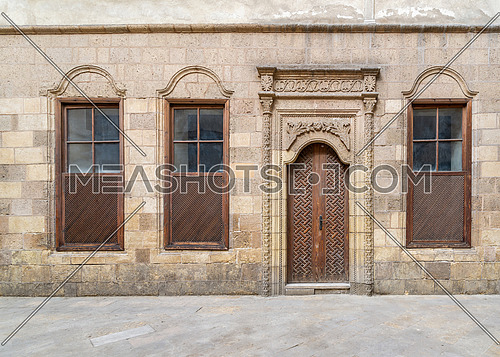 Facade of old abandoned stone decorated bricks wall with arched wooden door and three wooden shutter windows
