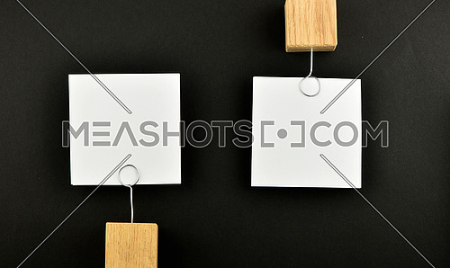 Opposite Opinion - Two white paper notes with wooden holders in different directions isolated on black paper background for presentation