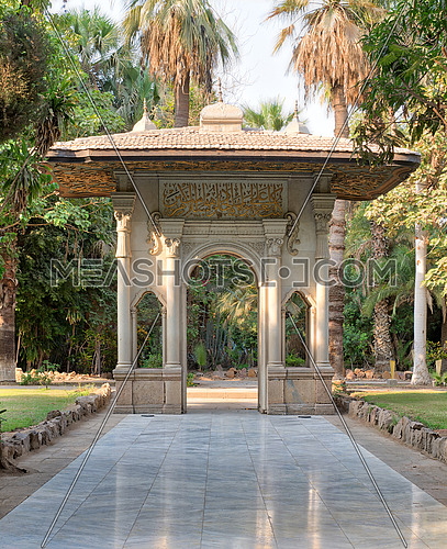 Porte-cochere (carriage porch, Gate) at the public park of Manial Palace of Prince Mohammed Ali Tewfik with marble tiled floor, trees and palms, Cairo, Egypt
