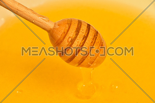Close up wooden honey dipper spoon in bowl of fresh thick fluid acacia honey, high angle view
