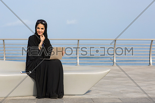 Saudi Lady wearing Black abaya working on her laptop by the sea at day.