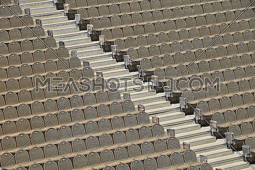 Rows of empty grey and red seats in open air concert hall auditorium, high angle side view