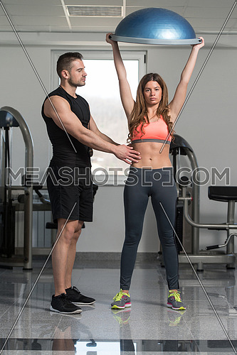 Personal Trainer Showing Young Woman How To Train On Bosu Balance Ball In A Gym