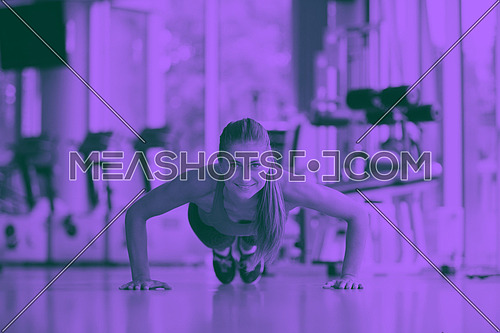 Gorgeous blonde woman warming up and doing some push ups a the gym duo tone