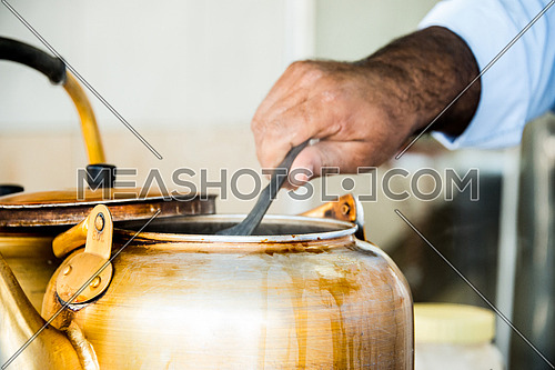 a man's hand pouring tea in foam cup