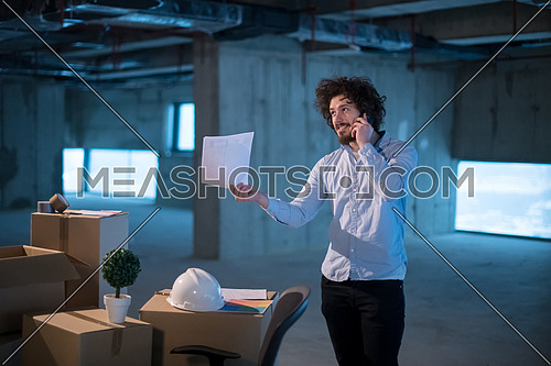 young male architect on construction site checking documents and business workflow using a mobile phone with cardboard boxes around him in new startup office