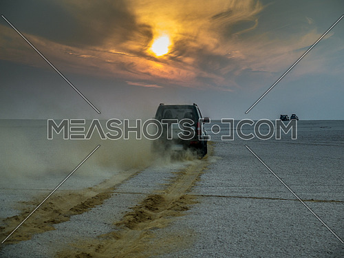 An SUV driving in the desert during sunset towards the horizon