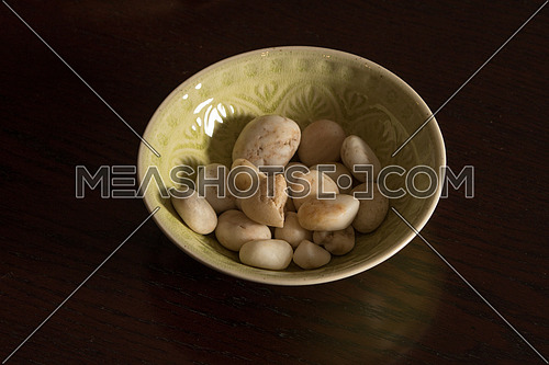 A green bowl with white peddles