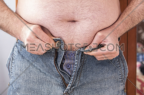 Overweight man trying to fasten too small clothes