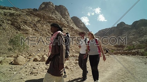 Follow shot for group of tourists walking with bedouin guide exploring Sinai Mountain from wadi Freij at day.