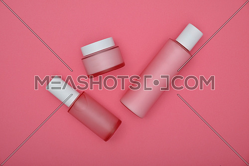 Close up set of three cosmetic skin care cream, lotion and tonic bottles over pink background, elevated top view, directly above