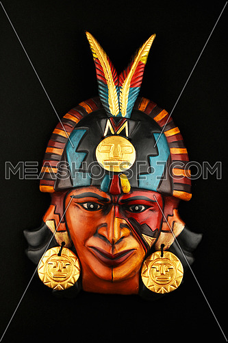 Indian Mayan Aztec ceramic mask with feather isolated on black paper background