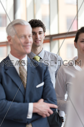 portrait of young business man with curly hair and  at modern bright office  interior with big windows in background and people group in front