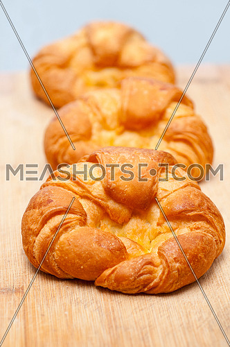 three fresh baked french croissant brioche on wood board