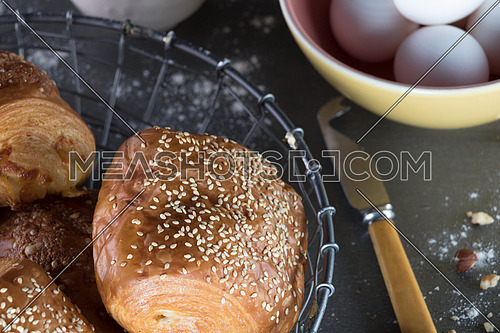 Pastry in a metal basket and yellow pink bowl filled with eggs and a knife aside
