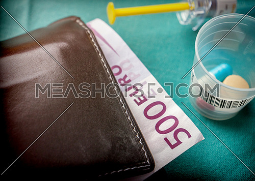 Wallet with dollar next to medicines, concept of copayment health