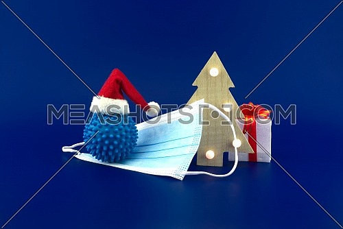 Christmas in pandemic concept still life with blue virus molecule, red Santa hat, Christmas tree and gift box sitting on face mask all isolated on blue background