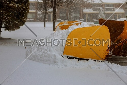 Snow sweeper works on the snowy street with a backhoe removes snow from