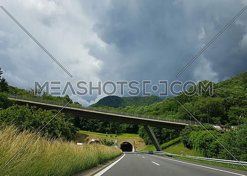 Freeway overpass in front of road tunnel in the mountains with thunderstorms in the background