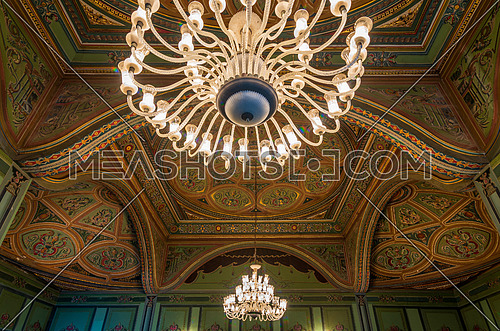 Ceiling at royal era historic Manasterly Palace decorated with colorful and golden floral paintings, and big lighted chandelier, Cairo, Egypt