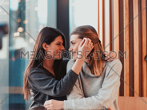 two LGBT girls romantically embracing sitting in a modern cafe. women's in an emotional embrace