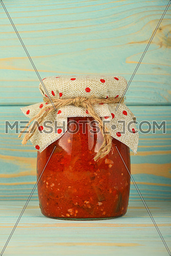 One glass jar of homemade pickled pepper, paprika and eggplant salad with dotted textile top decoration at blue painted vintage wooden surface