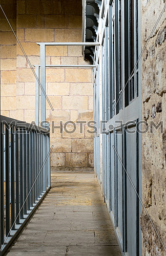 Narrow passage framed by blue wooden doors and balustrade leading to stone wall at historical traditional bathhouse (Hamam Inal), Cairo, Egypt