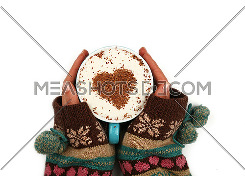 Close up two woman hands hold and hug big full cup of latte cappuccino coffee with heart shaped chocolate on milk froth isolated on white background, elevated top view, directly above