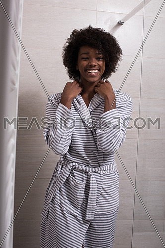 Portrait of young beautiful black woman wearing  bathrobe standing in the bathroom