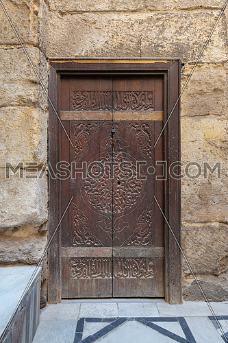 Wooden ornate door with geometrical engraved patterns on external old decorated bricks stone wall, Sultan Barquq mosque, Cairo, Egypt