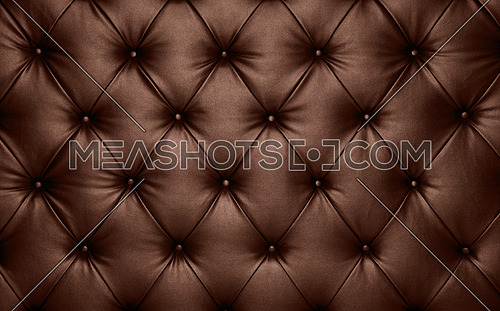 Close up background texture of dark brown capitone genuine leather, retro Chesterfield style soft tufted furniture upholstery with deep diamond pattern and buttons