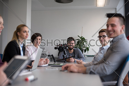 close up of  businessman hands  using tablet, people group in office meeting  room blurred in backgronud