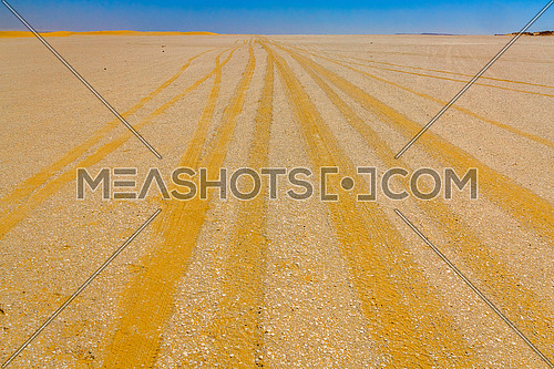 An off road track with yellow gravel and a blue sky