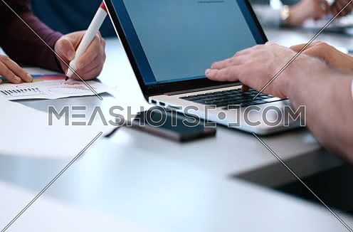 Young Businessman Hands Typing On Laptop Computer Keyboard then track left revealing female hands writing with red pen.