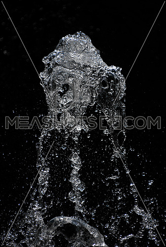 Fountain transparent water stream, splash and drops in motion over black background